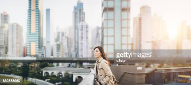 Confident corporate woman overlooking the cityscape of Hong Kong on urban balcony
