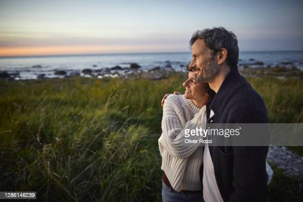 confident couple looking at view at the sea - holiday stock pictures, royalty-free photos & images