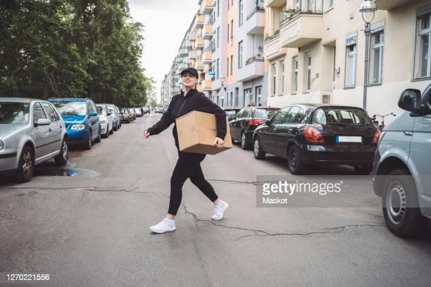 confident delivery woman with cardboard box walking on street in city - junge frau allein stock-fotos und bilder
