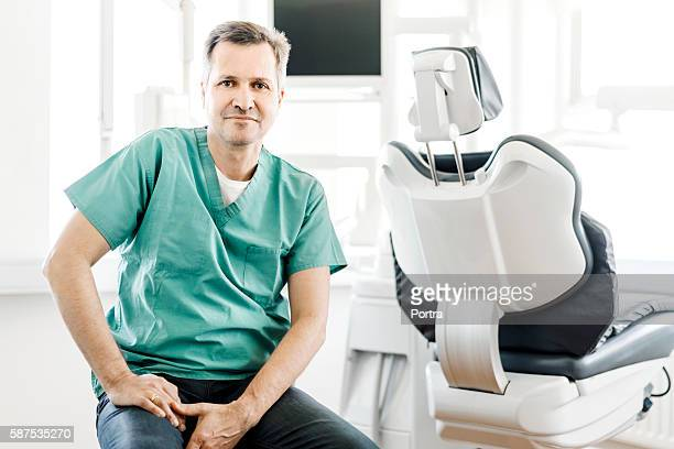 Confident dentist sitting by chair in clinic