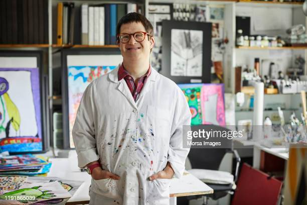 confident disabled male standing in art studio - disability stock pictures, royalty-free photos & images
