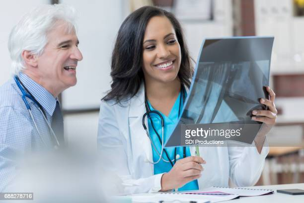 Confident diverse physicians review patient's x-ray