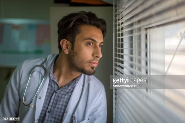 docteur confiant à la recherche par le biais de la fenêtre - irak photos et images de collection