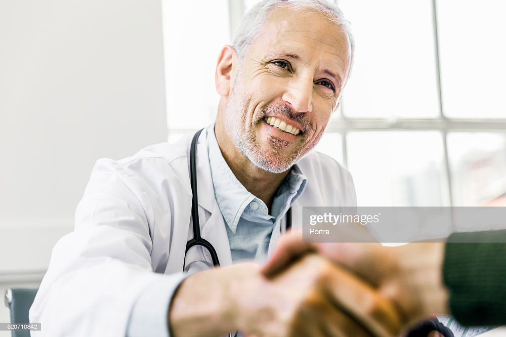 Confident doctor shaking hands with patient : Stock Photo