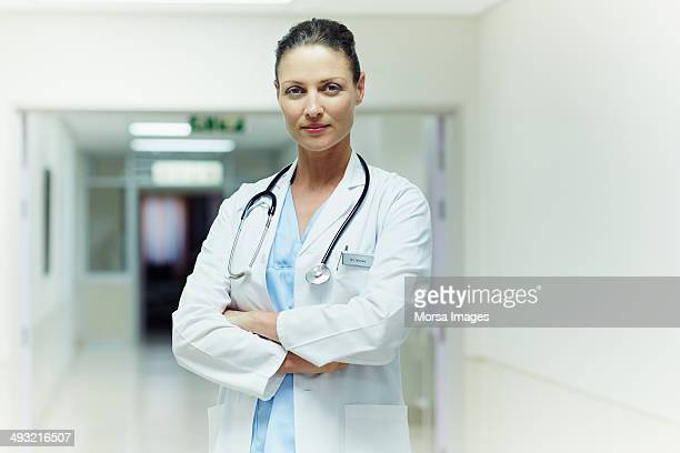 confident doctor standing arms crossed - female doctor stock photos and pictures