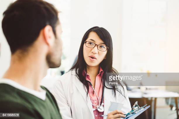 Zuversichtlich Arzt im Gespräch mit männlicher Patient in Klinik