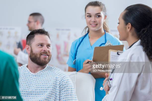 Confident doctor talks with patient during rounds