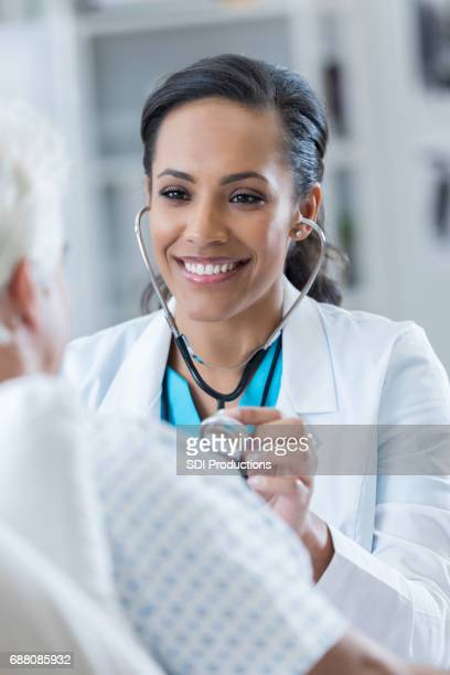 Confident doctor uses stethoscope in the hospital