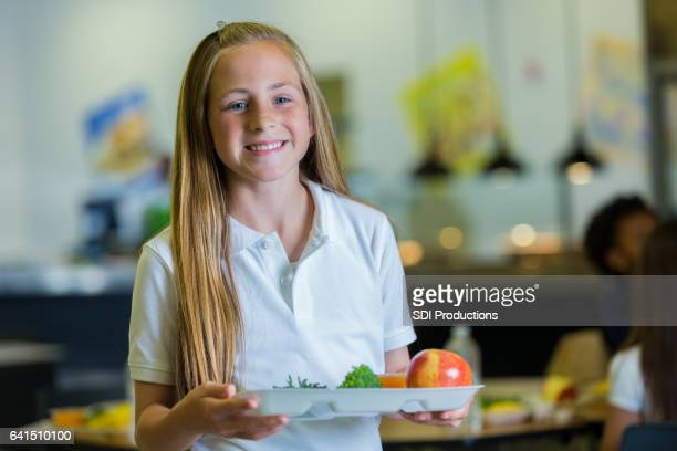 Confident elementary student with healthy lunch in cafeteria