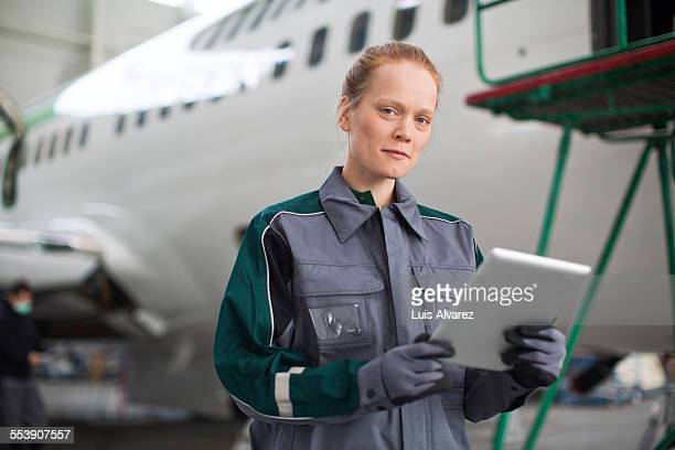 Confident engineer holding tablet PC in hangar