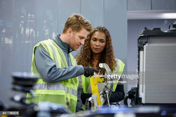confident engineers discussing over car chassis - mechanical engineering stock pictures, royalty-free photos & images