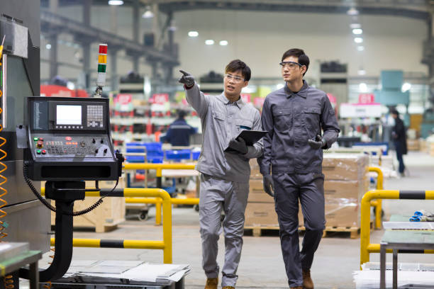 confident engineers talking in the factory - asian man factory worker stock pictures, royalty-free photos & images
