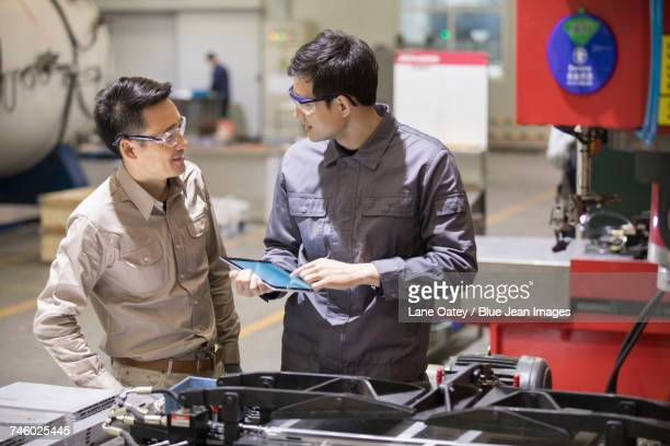 Confident engineers talking in the factory