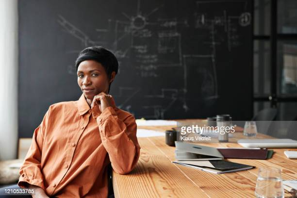 confident entrepreneur sitting in board room - attitude stock pictures, royalty-free photos & images