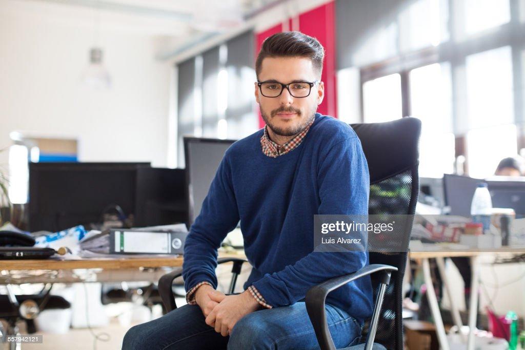Confident entrepreneur sitting in new office : Stock Photo