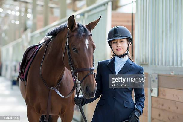 Confident equestrian with horse in stable