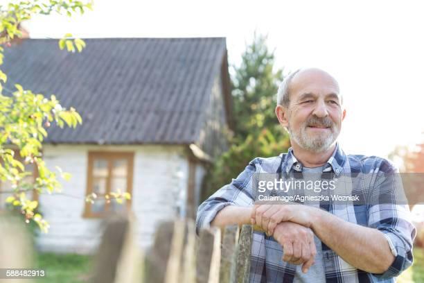 Confident farmer leaning on fence outside farmhouse