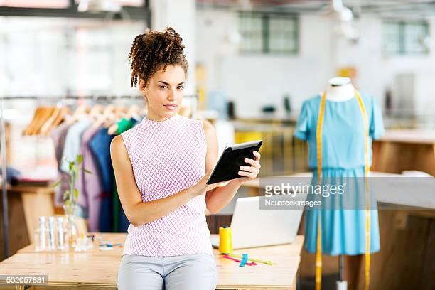 Confiant créateur de mode à l'aide de tablette numérique à l'atelier