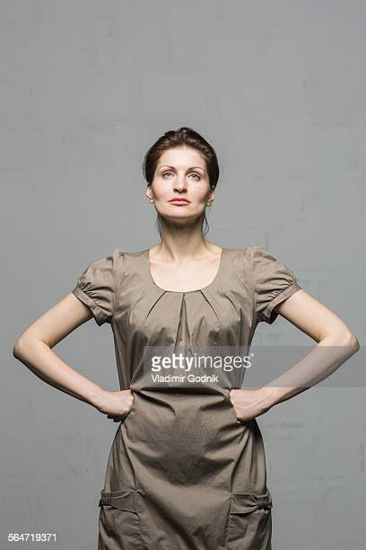 Confident fashion model standing with hands on hips against gray background