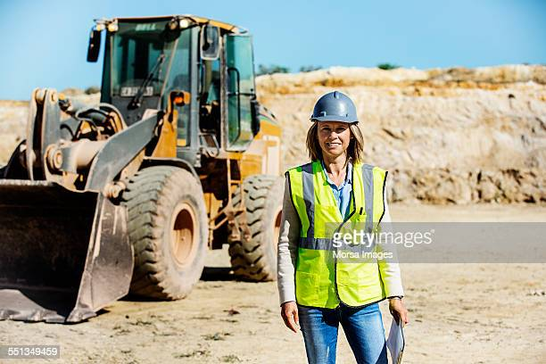 confident female architect standing at quarry - bulldozer stock pictures, royalty-free photos & images