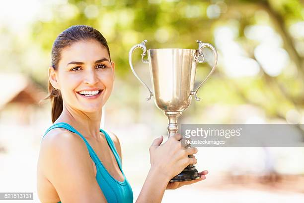 Confident Female Athlete Holding Trophy At Park