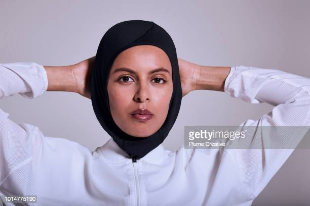 Confident female athlete looking to camera with hands behind head