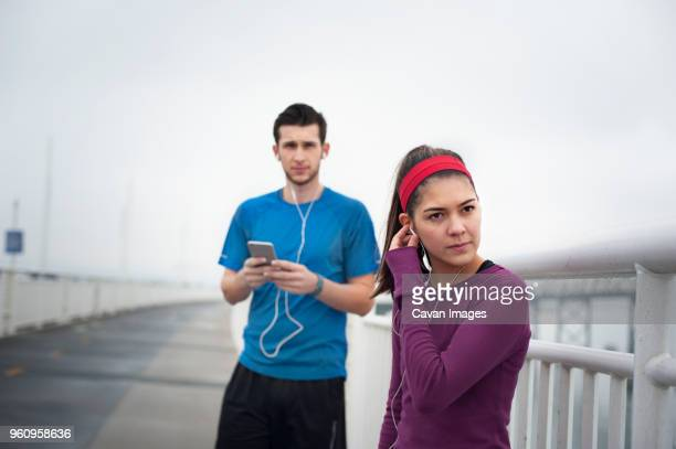 confident female athlete wearing earphones while standing with friend on bay bridge - headband stock pictures, royalty-free photos & images