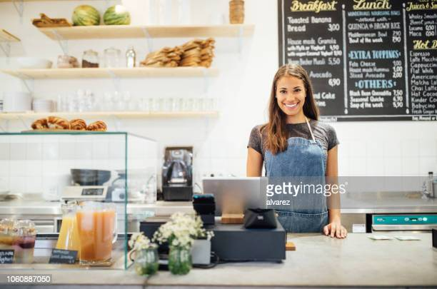 confident female barista standing behind cafe counter - cash register stock pictures, royalty-free photos & images
