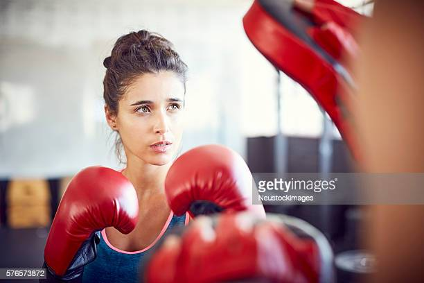 Confident female boxer practicing in health club
