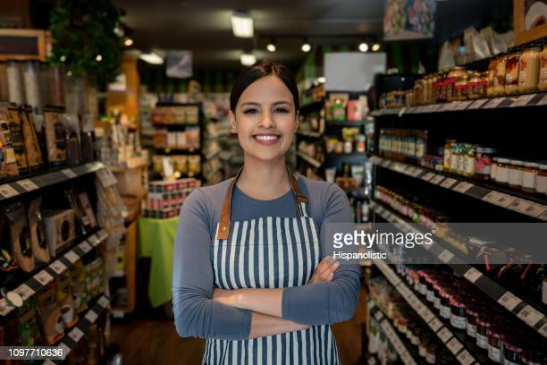 confident female business owner of a supermarket standing between shelves while facing camera smiling - business owner stock pictures, royalty-free photos & images