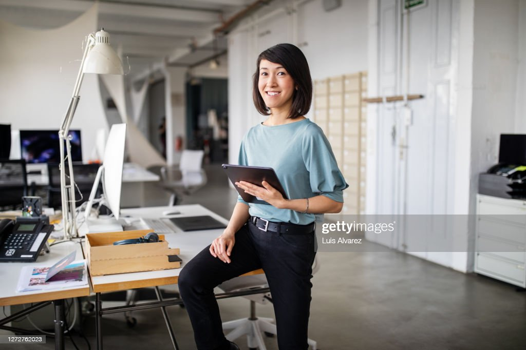 Confident female business professional with digital tablet : Stock Photo