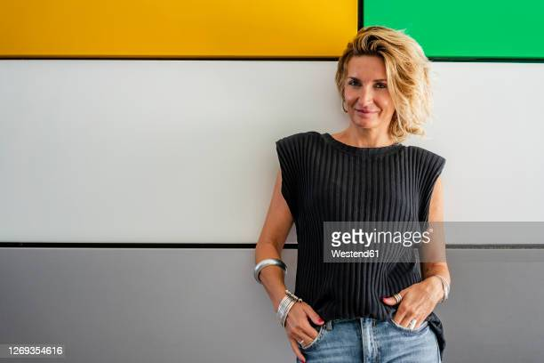 confident female chef standing with hands in pockets against colorful wall at cooking school - cool attitude stock pictures, royalty-free photos & images