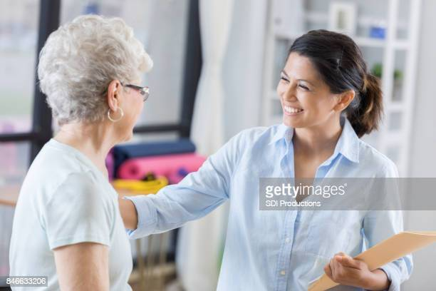 Confident female chiropractor talks with new patient