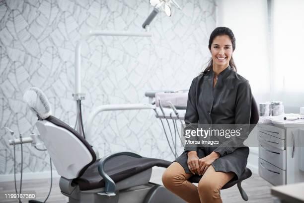 クリニックに座っている自信のある女性歯科医 - 歯科衛生士 ストックフォトと画像