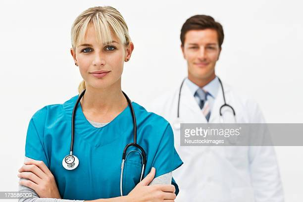 confident female doctor with colleague in background - nurse and portrait and white background and smiling and female and looking at camera stock pictures, royalty-free photos & images