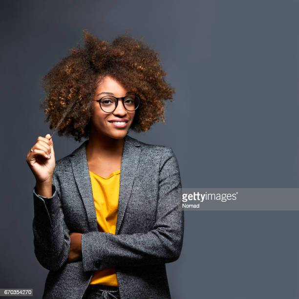 Confident female executive against gray background
