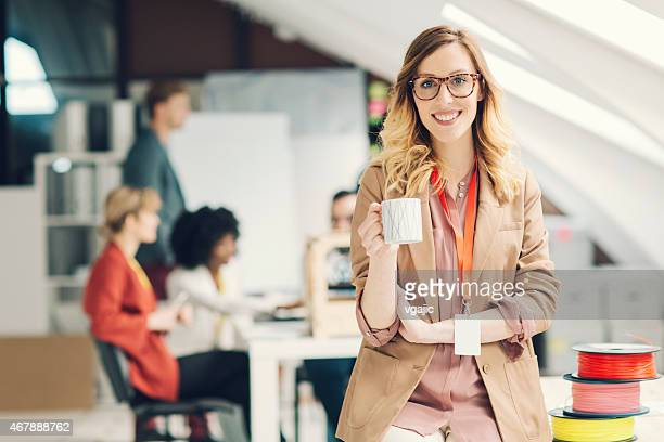 Confident female executive stand out in front of her team.