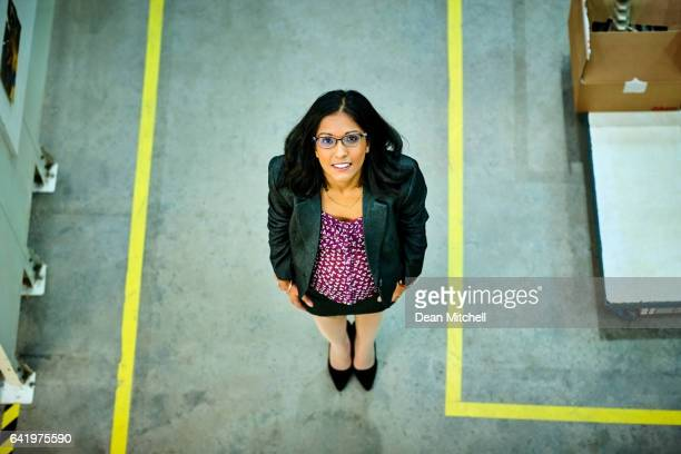 Confident female executive standing in warehouse