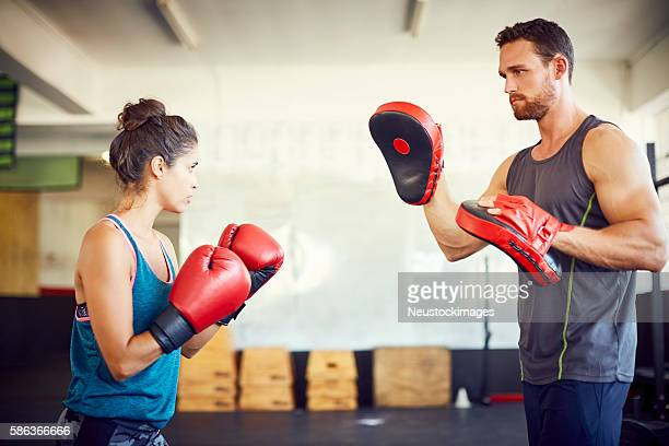 Confident female fit boxer practicing with coach in gym