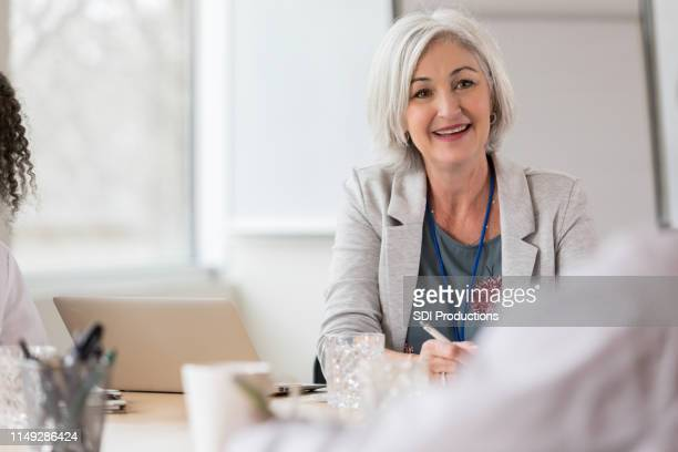 confident female hospital administrator facilitates meeting - administrator stock pictures, royalty-free photos & images