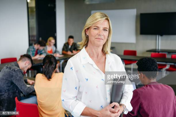 Confident female lecturer in classroom holding folder, looking at camera