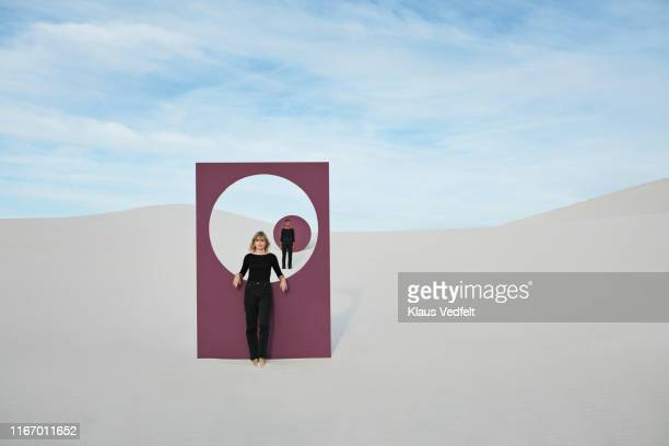 confident female models with portal standing at desert against sky - simple living stock pictures, royalty-free photos & images