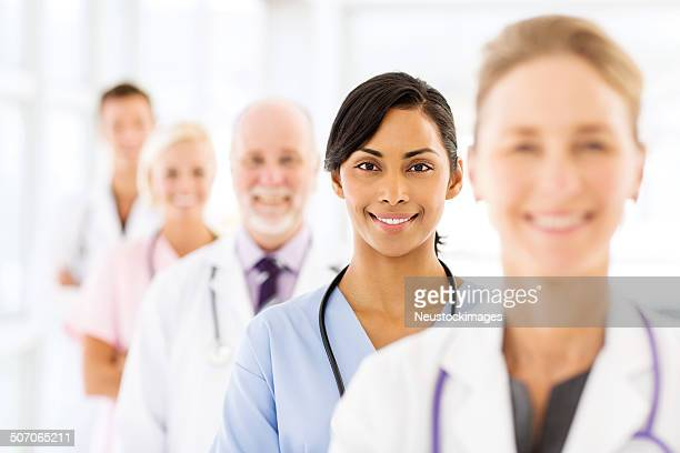 Confident Female Nurse With Medical Team In Hospital