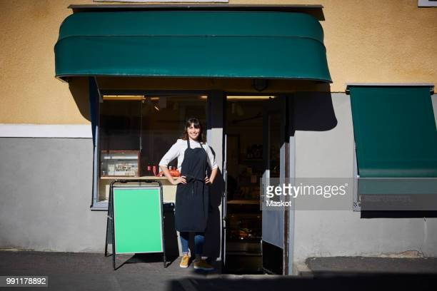 Confident female owner standing with hands on hips at entrance of store