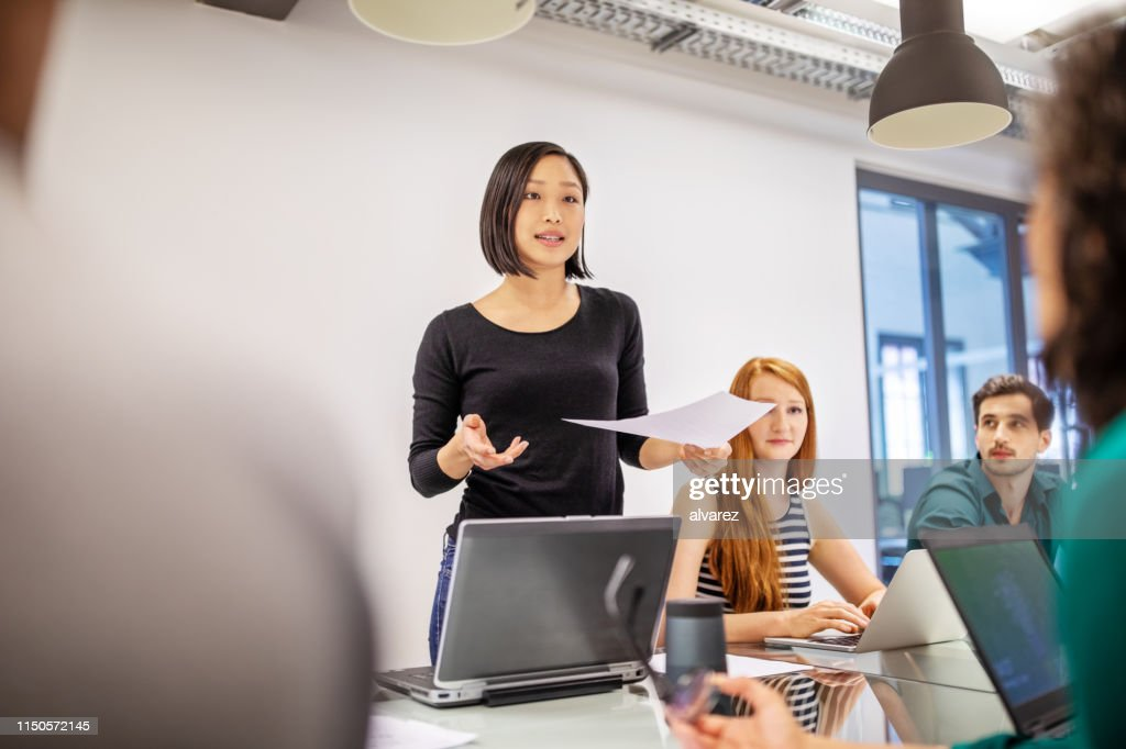 Confident female professional discussing with colleagues : Foto de stock