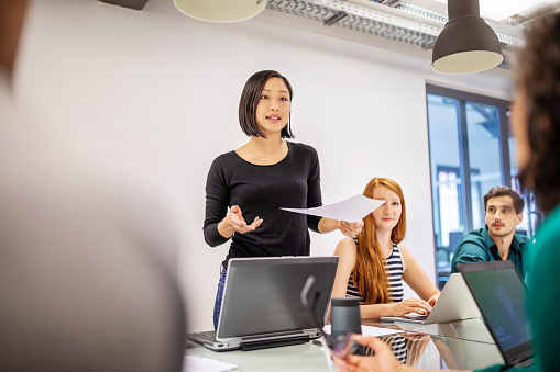 Confident female professional discussing with colleagues 1150572145