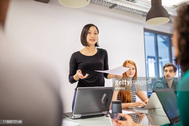 confident female professional discussing with colleagues - asian and indian ethnicities stock pictures, royalty-free photos & images
