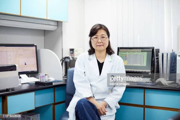 Confident female scientist sitting on chair in lab