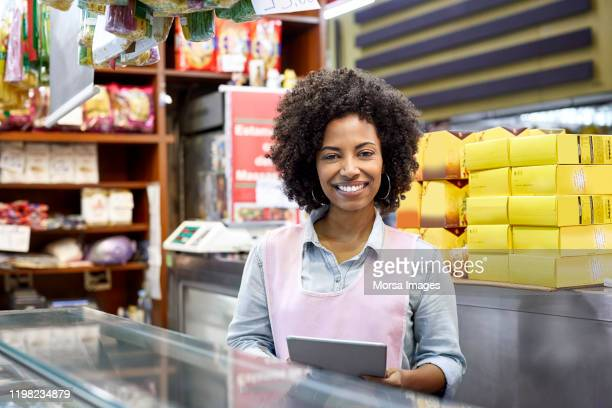 confident female store owner holding tablet - pardo brazilian stock pictures, royalty-free photos & images