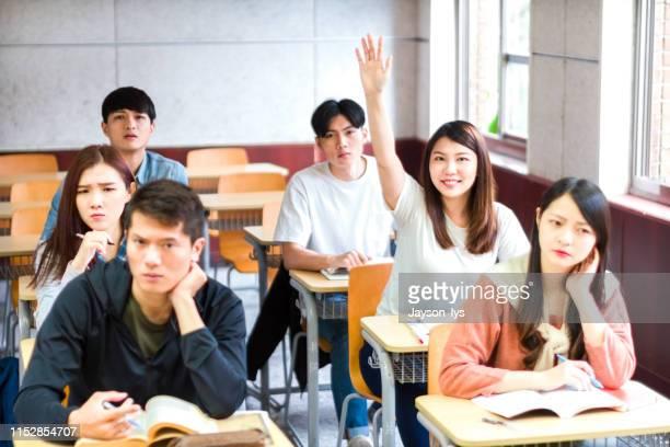 答えの質問に手を上げる自信のある女子学生 - 率先 ストックフォトと画像